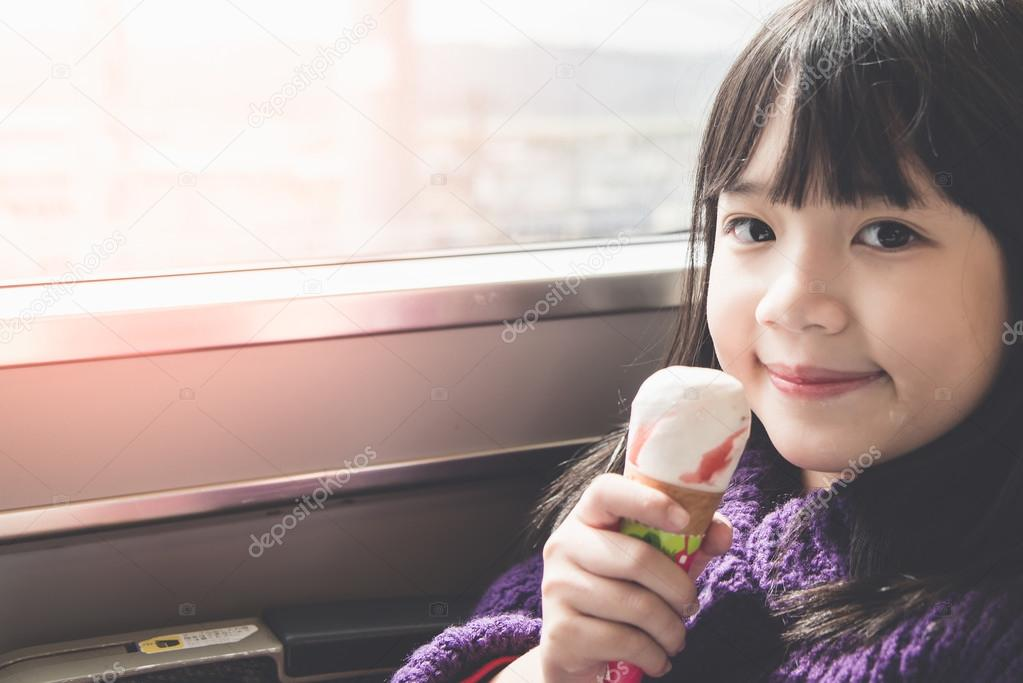 Little asian girl smiling  and eating ice cream