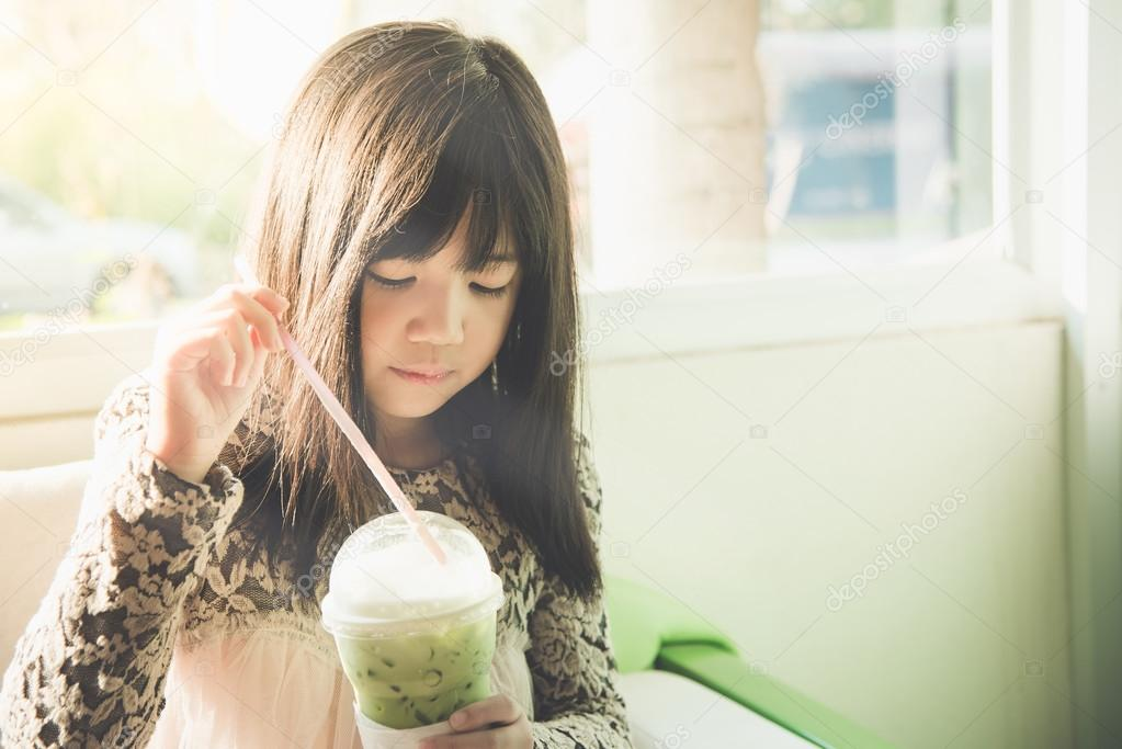 Beautiful asian girl drinking iced greentea