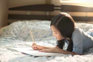 Beautiful asian girl writing to diary