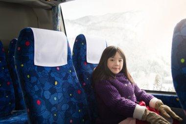 Little asian girl looking through window