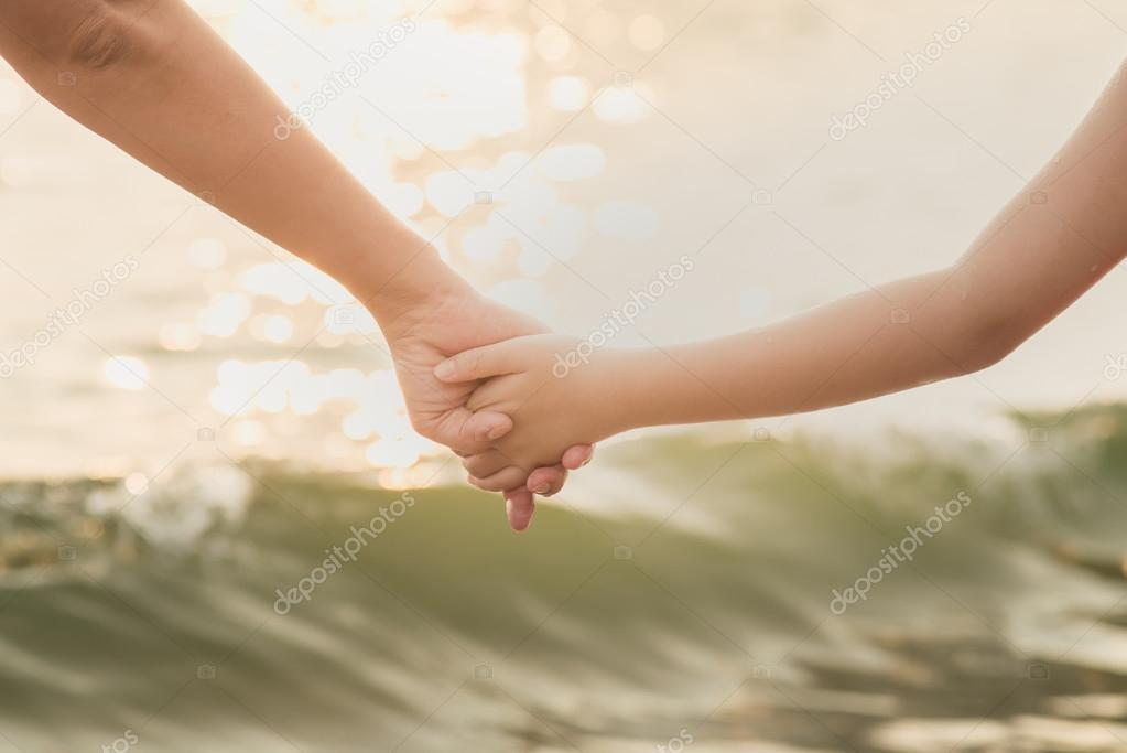 Hands of mother and son holding each other