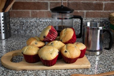 Freshly baked blueberry muffins with red wraping in a kitchen board