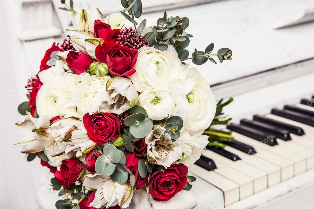 The bridal bouquet from roses lies on piano keys.