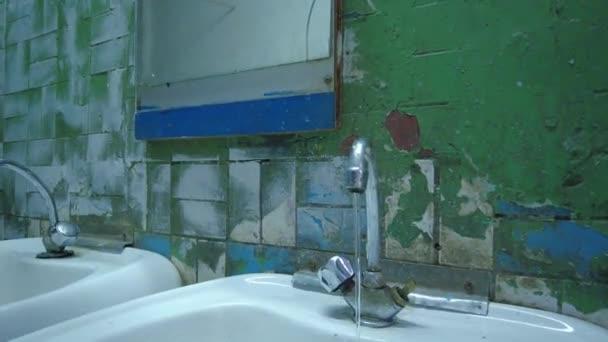 Víz csöpög a csapból a mosogatóba egy szobába morzsolódó csempe és penész egy régi ijesztő WC szoba és a mosogató