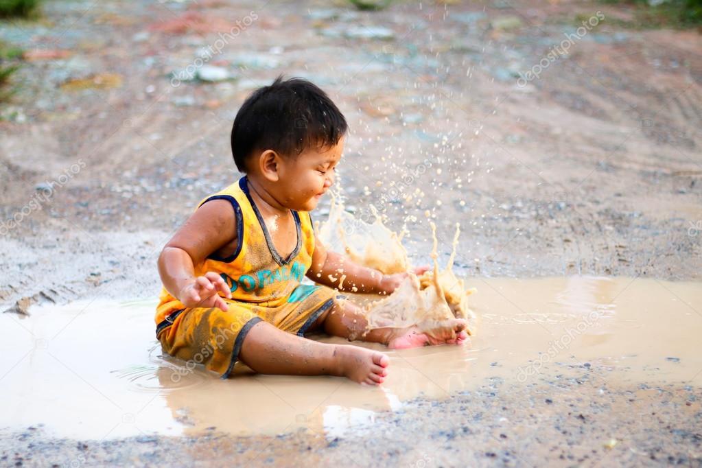 Children sitting in puddles