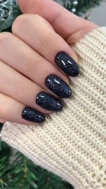Černá manikúra. Ruce ženy s černou manikúrou na nehty.Manikúra salon krásy koncept. Prázdné místo pro text nebo logo.