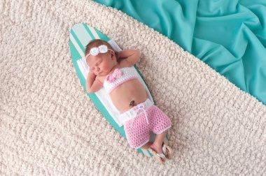 Newborn Baby Girl Sleeping on a Surfboard