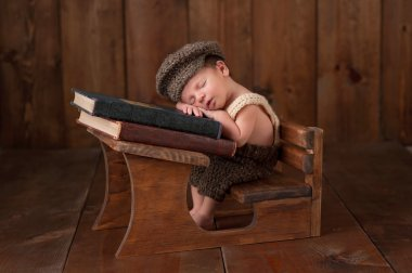 Newborn Baby Boy Sleeping at his School Desk