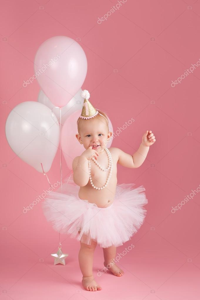A Portrait Of Smiling One Year Old Baby Girl Wearing Pink Tutu String Pearls And Birthday Hat She Is Standing On Seamless Background With