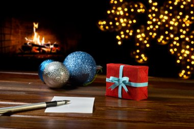 Letter to Santa Claus near the gift and candles