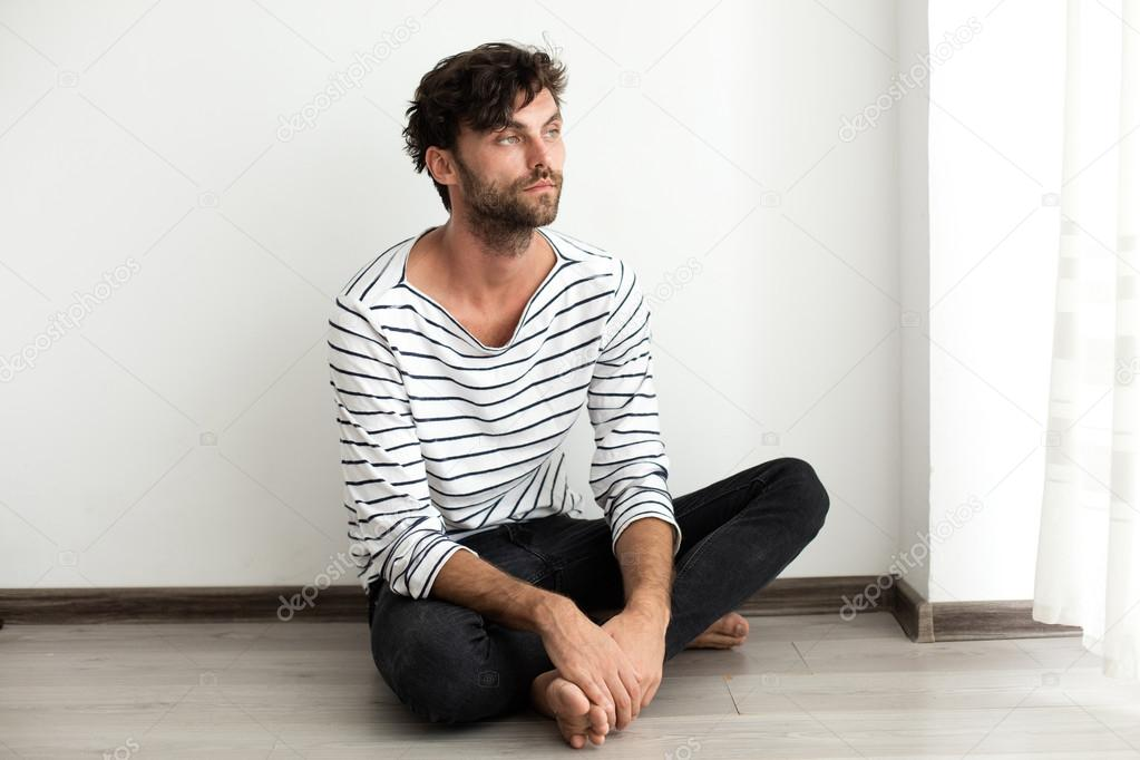 Handsome man in stripes sitting down on