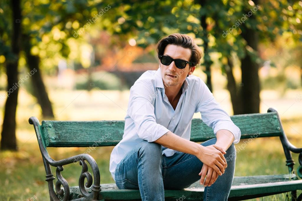 attractive man sitting alone on the bench with cellphone