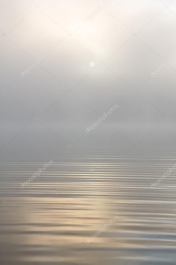 Morning sun through fog at lake