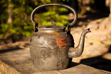 Old kettle in wooden bench outdoors