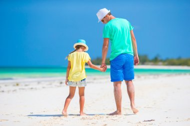 Little girl and young father during tropical beach vacation