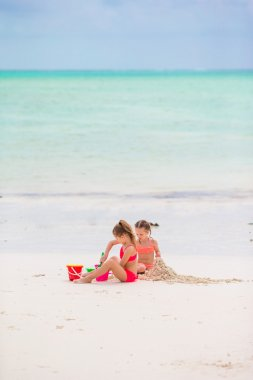 Little kids playing with beach toys on tropical vacation