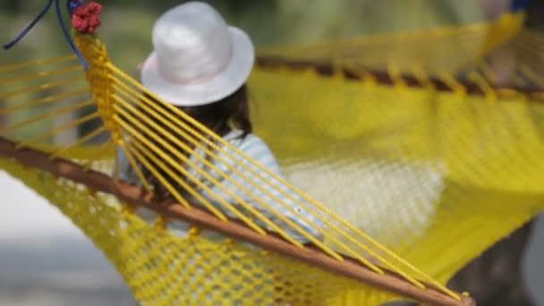 krásná žena odpočívat v houpací síti na tropické pláži