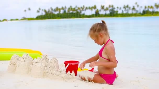 Little girl playing with beach toys during tropical vacation