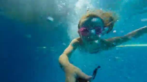 Underwater happy beautiful girl in swimming pool having fun