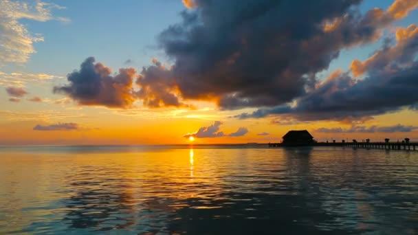 Temné siluety palem a úžasné zamračená obloha na západ slunce na tropický ostrov v Indickém oceánu