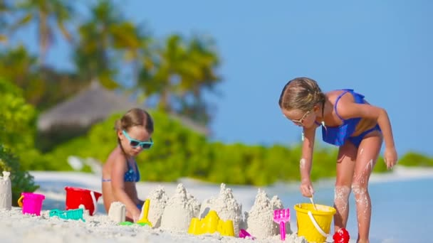 Little girls playing with beach toys during tropical vacation