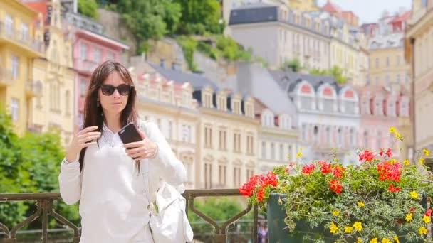 Mladá žena se autoportrétem pozadí krásného domu v evropském městě. Kavkazské turistické těšit její evropské letní dovolenou v Evropě.