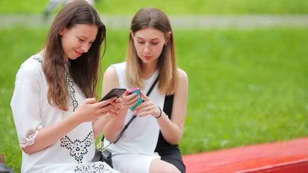 Two young girls using smart phone outdoors. Two women sitting in park with coffee and using smartphone
