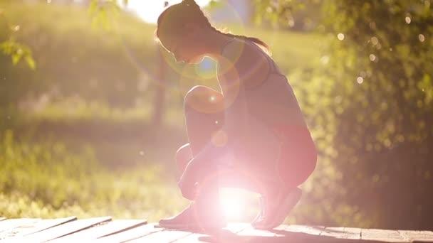 Mladý aktivní žena, šněrování světle růžové a modré tenisky v měkké světlo. Běžecké boty - záběr ženy, vázání tkaničky