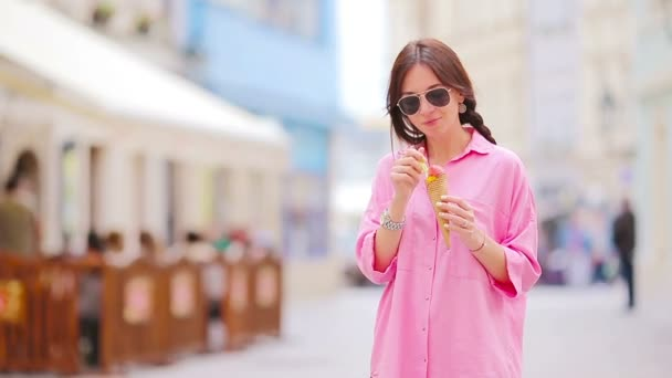 Young female model eating ice cream cone outdoors. Summer concept - woman with sweet ice-cream at hot day