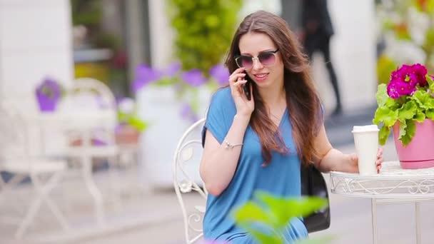 Boldog lány divat beszél telefonon openair kávézóban kávét vásárlás után. Eladó, a fogyasztás és a nép fogalmát. Kaukázusi lány élvezze a szabadtéri kávézóban meleg nap.