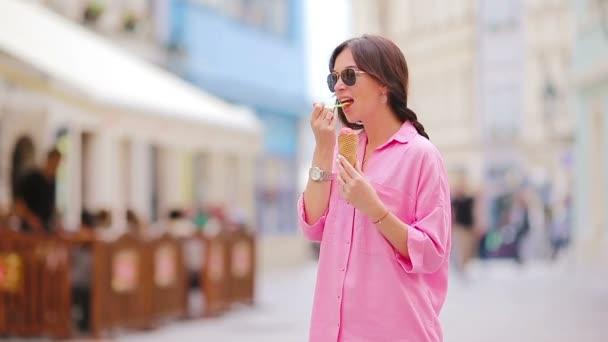 Mladá modelka jí zmrzlinu venku. Letní koncept - vlna se sladkou zmrzlinou v horkém dni