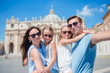 Happy young family taking selfie at St. Peters Basilica church in Vatican city, Rome. Happy travel parents and kids making selfie photo picture on european vacation in Italy.
