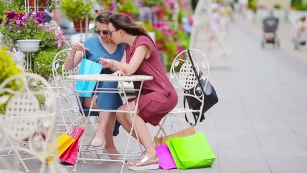 Dva módní barevné nakupující tašky nákupní v kavárně openair. Prodej, konzumu a lidé koncept. Kavkazská děvčata si jejich teplý den ve venkovní kavárně