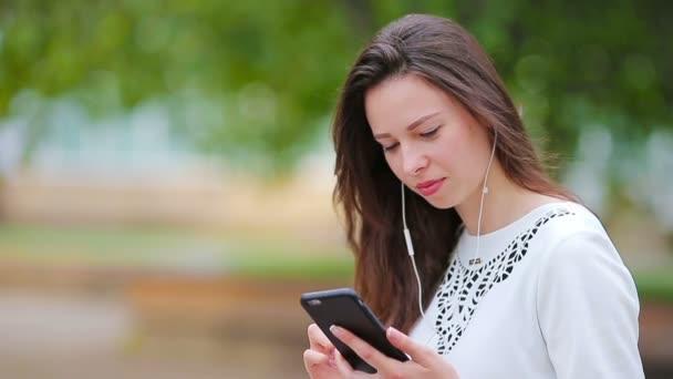 junge kaukasische Frau, die draußen im Park mit ihrem Smartphone Nachrichten sendet. Schönes Mädchen mit Sonnenbrille sitzt mit Smartphone auf Holzbank