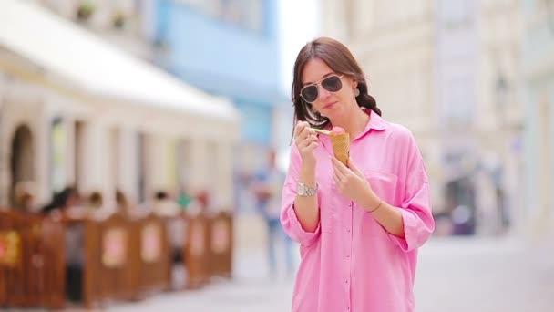 Mladá dívka jí zmrzlinu venku. Letní koncept - žena se sladkou zmrzlinou v horkém dni