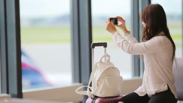 Cestující v letadle na letišti lenošit, čeká na letu letadel a pořizování fotografií z letiště. Kavkazský žena s smartphone v čekárně
