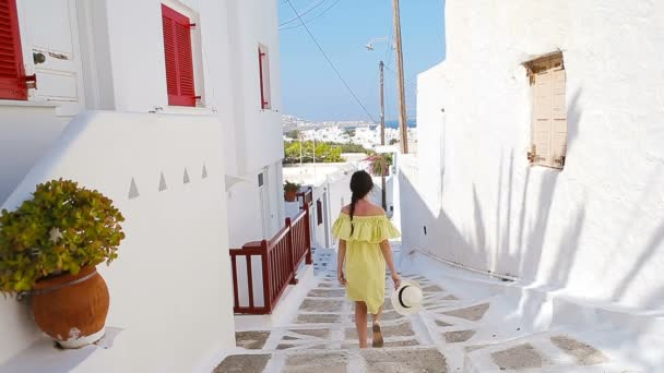 Beautiful woman outdoors in old streets an Mykonos. Girl at street of typical greek traditional village with white walls and colorful doors on Mykonos Island, in Greece, Europe
