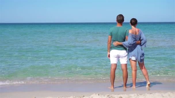 Mladý pár na bílé pláži během letní dovolené.