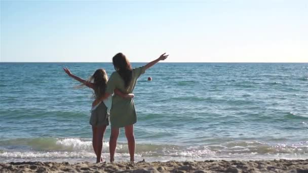 Beautiful mother and daughter on the beach enjoying summer vacation