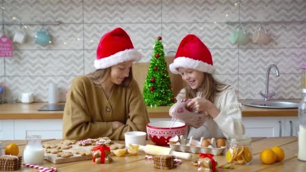 Dívky dělat vánoční perník dům u krbu ve zdobeném obývacím pokoji.