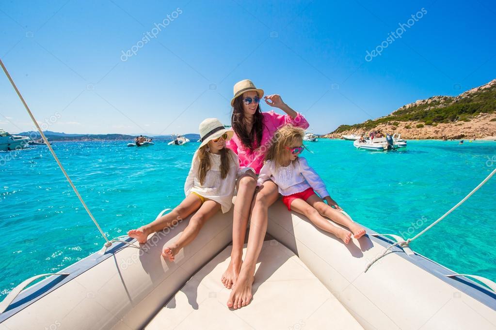 Giovane madre con le sue adorabili bambine che riposano su una grande barca
