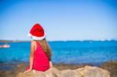 Fényképek Hátulnézet a santa kalap-aranyos kis lány a strandon