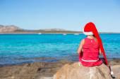 Fényképek aranyos kislány santa kalapját, és ül a nagy kő piros ruha