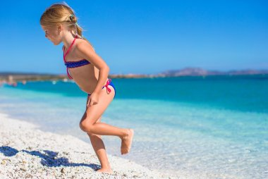 Adorable little girl in shallow water have fun at white beach
