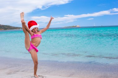 Smiling little girl making stretching exercise in Santa Hat on white beach