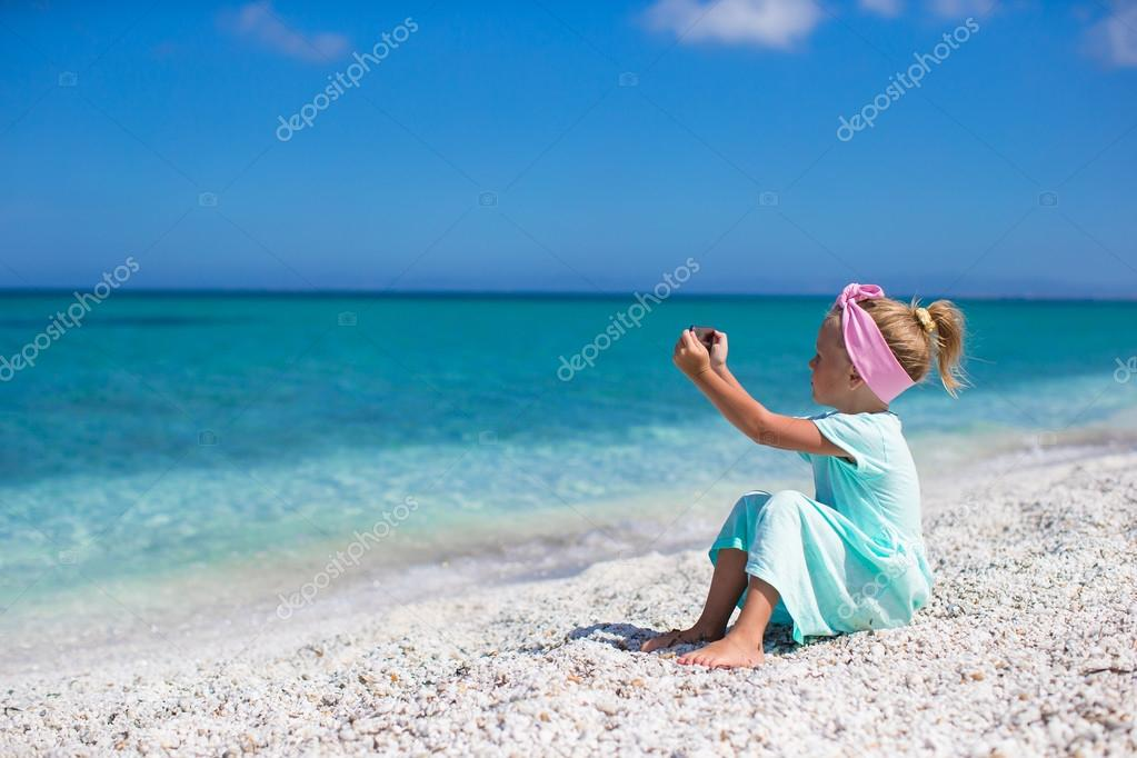 Little cute girl take a picture on phone at tropical beach