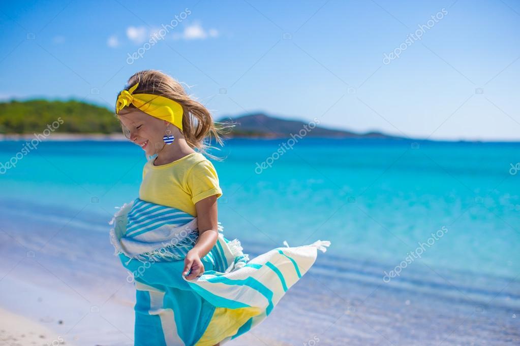 petite fille avez amusant avec serviette de plage et très heureux ...