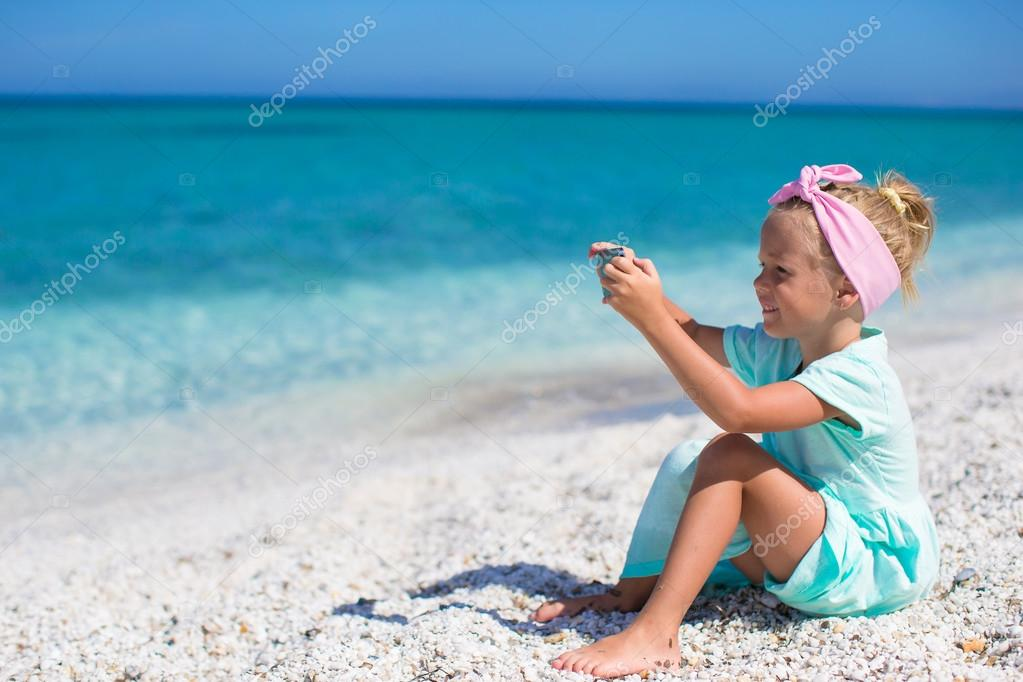 Little cute girl taking pictures on the phone at tropical beach