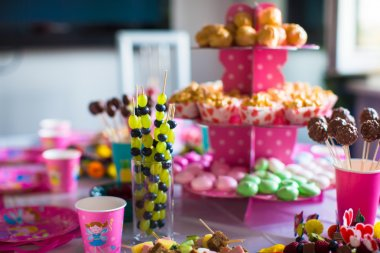 Canape of fruit, white chocolate cake pops and popcorn on sweet childrens table at birthday party