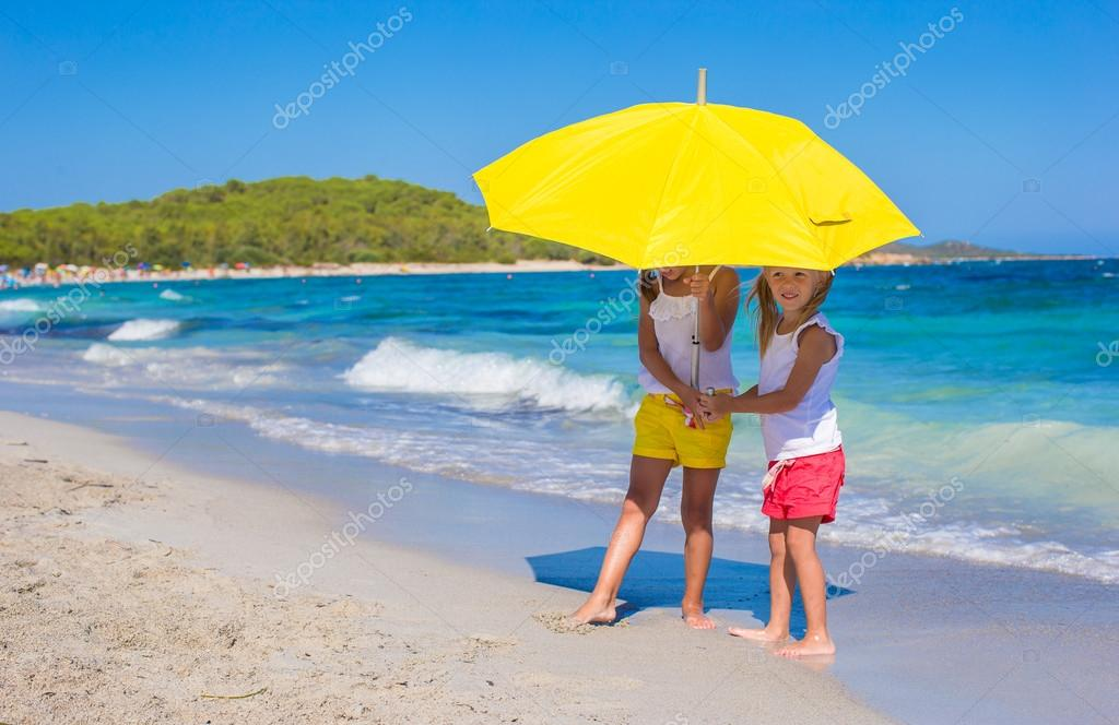 15f026b1e0880 Little girls with big yellow umbrella walking on tropical beach — Stock  Photo